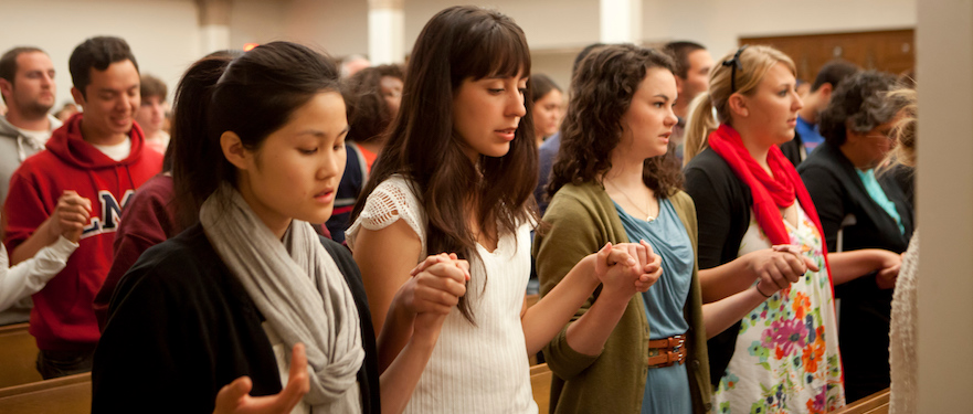 Students in mass holding hands in prayer.
