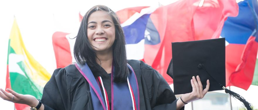 Student graduating with international flags in the background